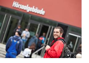 Junger Mann steht vor der Hochschule. (Foto: Swen Reichhold)