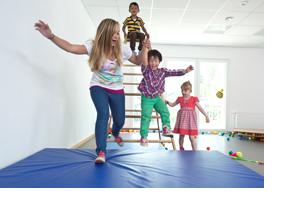Kinder, die auf einer Sportmatte herumhüpfen. (Foto: Axel Jusseit)