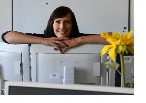 Frau steht lächelnd hinter ihrem Monitor. (Foto: Christof Stache)