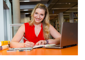 Frau sitzt vor ihrem Laptop und macht sich Notizen in einem Buch. (Foto: Karsten Socher)