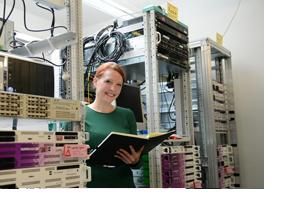 IT-Expertin steht zwischen Server-Schränken. (Foto: Christof Stache)