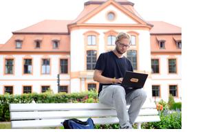 Studierender sitzt mit dem Laptop auf einer Parkbank. (Foto: Julien Fertl)