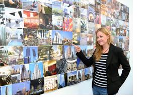 Junge Frau steht vor einer Fotowand mit Urlaubsbildern. (Foto: Martin Rehm)