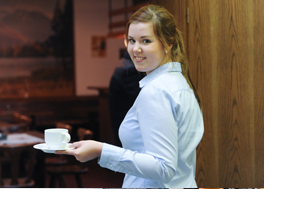 Junge Frau serviert eine Tasse Kaffee. (Foto: Nancy Heusel)