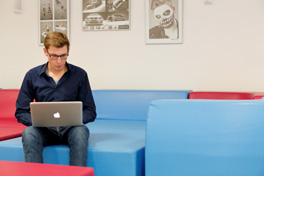 Ein junger Mann sitzt mit Laptop auf einer Couch. (Foto: Thorsten Ulonska)