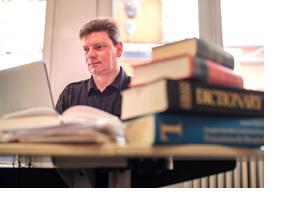 Ein Mann sitzt hinter einem Laptop; neben ihm liegen Wörterbücher. (Foto: Thomas Lohnes)
