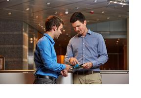Zwei Männer unterhalten sich über ein elektronisches Werkstück. (Foto: Sebastian Reimold)