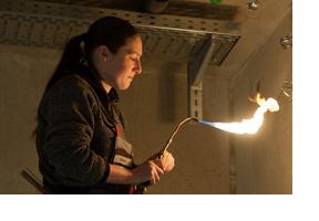 Eine Mechatronikerin lötet an einem Kupferrohr. (Foto: Armin Weigel)