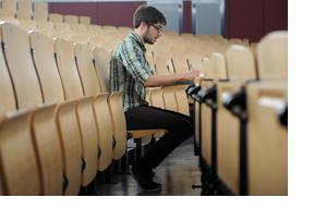 Ein junger Mann sitzt in einem Vorlesungssaal. (Foto: Christiane Specht)