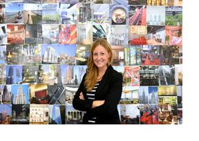 Eine Frau steht vor einer Wand mit Postkarten. (Foto: Martin Rehm)