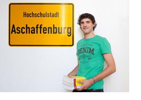 Studierender steht vor einem Ortsschild von Aschaffenburg. (Foto: Alex Becker)