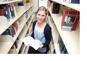 Eine Studentin liest ein Buch in einer Bibliothek. (Foto: Hans-Martin Issler)