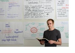 Ein Mann unterrichtet vor einen Plakatwand. (Foto: Christof Stache)