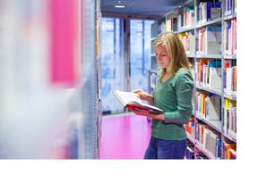 Eine Studentin liest ein Buch in der Bibliothek. (Foto: Andreas Franke)