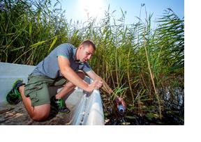 Ein junger Mann nimmt eine Wasserprobe. (Foto: Andreas Franke)