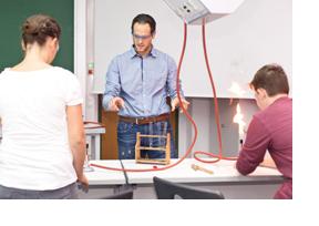 Ein Chemielehrer führt einen Versuch mit seinen Schüler/-innen durch. (Foto: André Braun)
