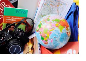 Verschiedene Utensilifür eine Fernreise: Fotoapparat, Klamotten Wörterbuch etc.. (Foto: Julien Fertl)