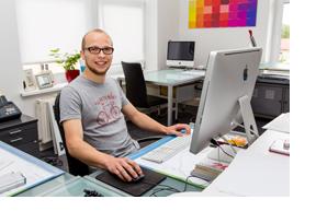 Ein Mediengestalter sitzt vor einem PC. (Foto: Helge Gerischer)