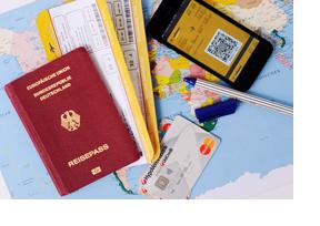 Reisepass, Kreditkarte, Handy und Flugtickets liegen auf einer Weltkarte. (Foto: Julien Fertl)