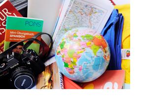 Ein Globus, eine Kamera, Landkarten und Wörterbücher. (Foto: Julien Fertl)