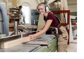 Eine Schreinerin sägt ein Holzbrett. (Foto: Julien Fertl)