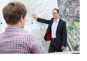 Ein Mann zeigt einem anderen Mann etwas auf einer Landkarte. (Foto: Friso Gentsch)