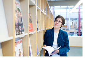 Eine junge Frau auf ein Zeitschriftenregal einer Bibliothek. (Foto: Andreas Tamme)