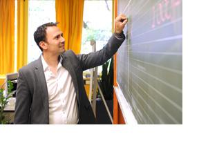 Ein Lehrer schreibt an eine Tafel. (Foto: Martin Rehm)