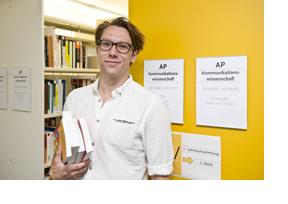 EIn junger Mann mit Büchern im Arm in einer Bibliothek (Foto: Hans-Martin Issler)