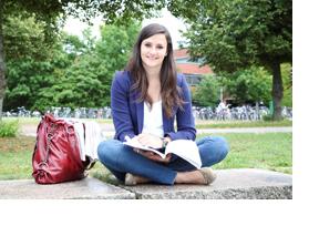 Studentin stitzt mit Buch auf einer Mauer. (Foto: Jessica Braun)