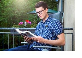 Ein Student sitzt mit Buch auf einem Stuhl. (Foto: Andreas Franke)