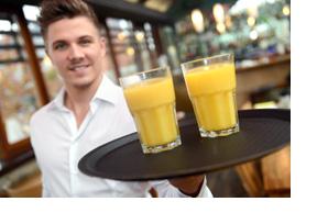 Ein Kellener hält ein Tablett mit zwei Orangensaftgläser in die Kamera. (Foto: Martin Rehm)