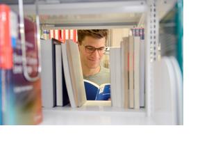 Ein Student schaut in ein Buch. (Foto: Nicole Schwab)
