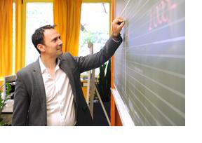 Ein Lehrer schreibt etwas an eine Tafel. (Foto: Martin Rehm)