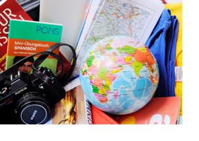 EIne Reisetasche mit Fotoapparat, GLobus und Reisebüchern. (Foto: Ann-Kathrin Hörrlein)