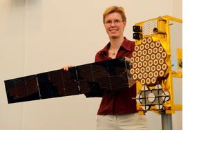 Frau hält das Seitenteil eines Satelliten in Händen. (Foto: Christof Stache)