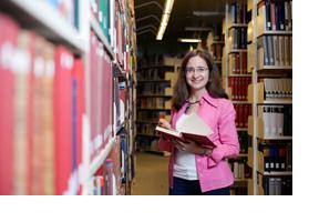 Eine Studentin liest ein Buch in einer Bibliothek. (Foto: Julien Fertl)