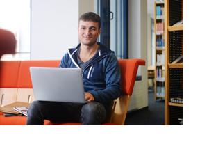 Ein junger Mann sitzt mit Laptop auf einer Couch. (Foto: Julien Fertl)