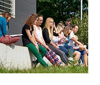 Studierende sitzen gemeinsam auf einer Mauer.