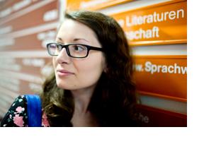 Eine Studentin steht vor Wegweisern in einer Uni. (Foto: Johannes Simon)