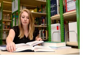 Eine Studentin sitzt vor Büchern in einer Bibliothek. (Foto: Frank Pieth)