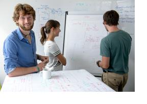 Drei Menschen stehen vor einen Flipchart und besprechen sich. (Foto: Thomas Lohnes)