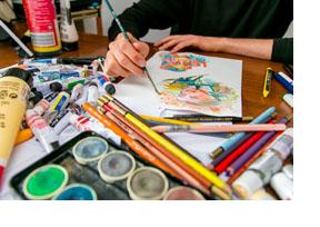 Eine Person malt mit Wassermalfarben Comicfiguren. (Foto: Helge Gerischer)