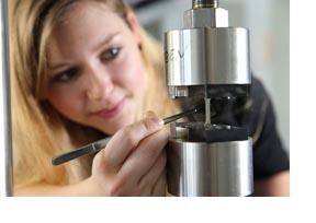 Eine Werkstoffwissenschaftlerin untersucht ein Materialstück. (Foto: Daniel Karmann)