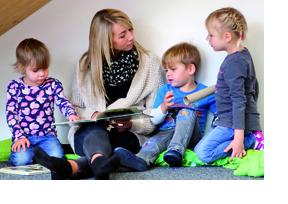 EIne Freiwillige liest drei Kindern etwas vor. (Foto: BA-Vertrag)