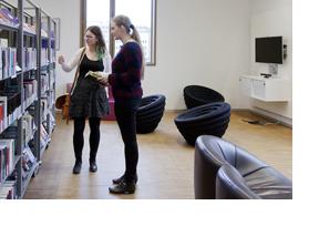 Zwei junge Frauen in einer Bibliothek. (Foto: BA-Vertrag)