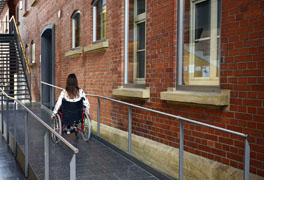 Eine Rollstuhlfahrerin fährt eine Rampe hoch. (Foto: Bundesagentur für Arbeit / Martin Rehm)