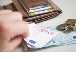 Eine Hand zählt Geldscheine und Münzen. (Foto: Bundesagentur für Arbeit)